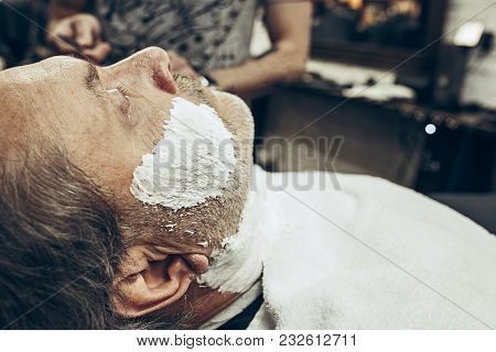 Close-up Side View Portrait Of Handsome Senior Bearded Caucasian Man Getting Beard Grooming In Moder