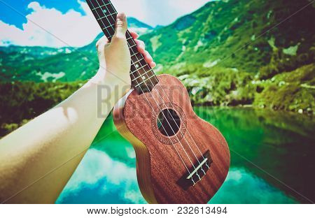 Romantic View Of The Ukulele Guitar Hold In A Hand, Mountains On Background . Photo Depicts Musical