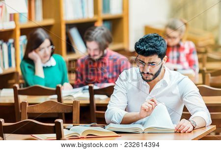 Portrait Of Successful Bearded Student Man Wears White Shirt Studying With Books In The Library