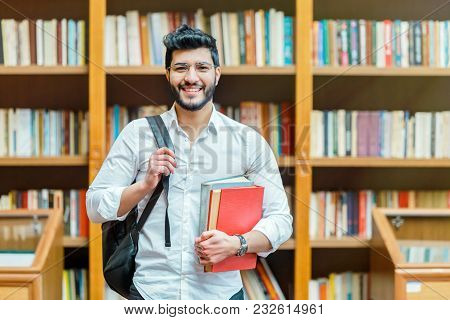 Portrait Of Young Bearded Man Student Holding Books Before Bookshelves In The Library