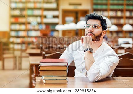 Portrait Of Young Thinking Bearded Man Student With Stack Of Books On The Table Before Bookshelves I