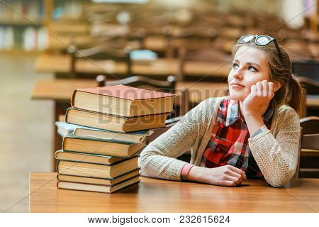 Portrait Of Student Girl Wears Glasses With Stack Of Books On The Table In The Library Reading Hall