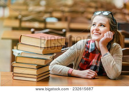 Portrait Of Student Smiling Girl Wears Glasses With Stack Of Books On The Table In The Library Readi