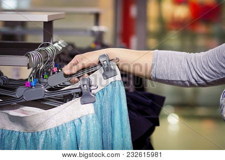 Close-up Of Hand Of Girl Takes Clothes On Hanger In Fashionable Clothes Boutique. Shopping Concept.