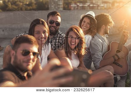 Group Of Young People Playing The Guitar, Singing And Taking Selfies At A Rooftop Party. Focus On Th