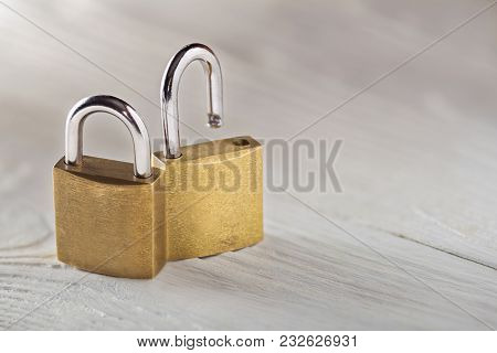 Two Padlock, Lock And Unlock, With Silvered Keys On White Wooden Background. Estate And Security Con