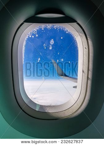 Photo Of Porthole With View To Wing Of Airplane, Blue Sky
