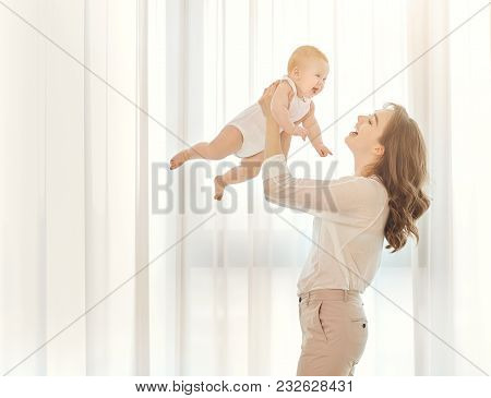 Mother With A Baby In Her Arms Plays Against The Window. Mothers Day.