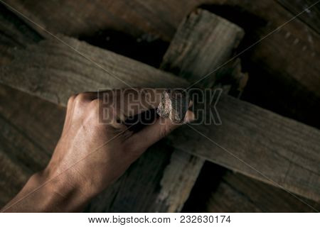 closeup of a young man driving a rusty nail on a wooden cross