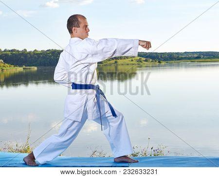 Sportsman Karate With Blue Belt Beats Punch Arm