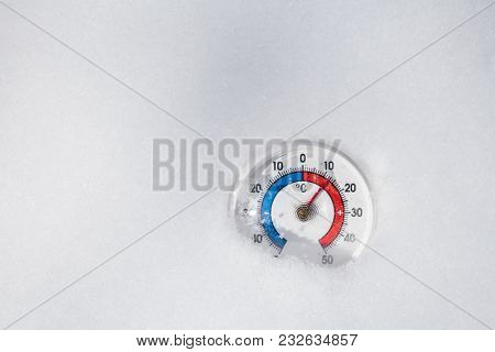 Thermometer with celsius scale in melting snow showing plus 12 degree temperature warm spring weather or global warming concept