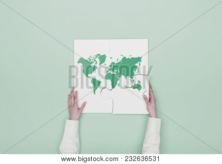 Woman Completing A Puzzle With A World Map