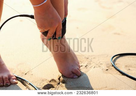 Surfer Girl Fastens The Leash To The Leg On The Beach