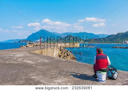 Keelung, Taiwan - April 04: Local Fisherman Sitting On A Wave Barrier Catching Fish In Badouzi Coast