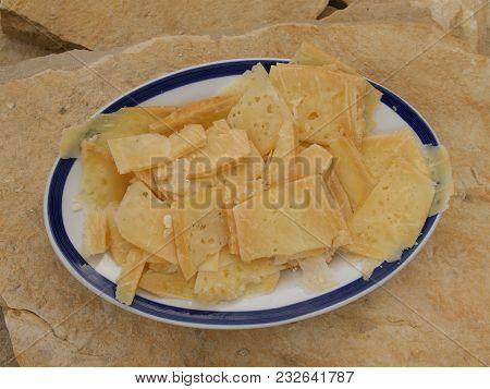 Sliced Cheese On The Plate Outdoor With Stone Background