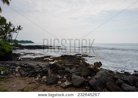 Beach And Lava Rock With A Nice Surf Spot At Kona Hawaii On The Big Island.
