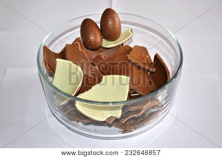 Easter Eggs Chocolate. Cracked Eggs Chocolate Of Glass Container, White Background. Milk And White C
