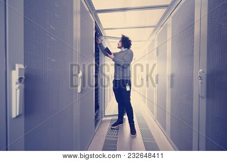 young IT technician using digital cable analyzer on server in large data center