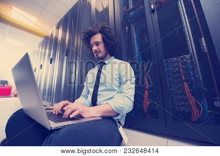 Male IT engineer working on a laptop in server room at modern data center