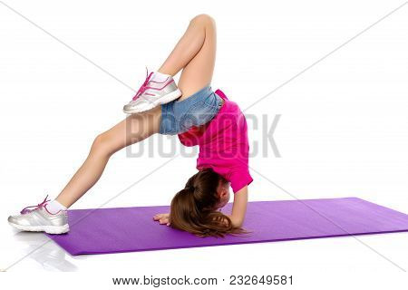A Girl Gymnast Performs An Exercise Stance On Her Forearms.the Concept Of Childhood, Sport, A Health