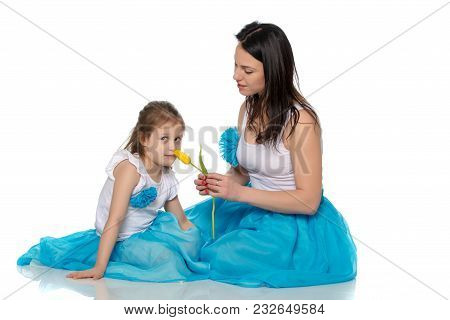 Beautiful Young Mother And Little Daughter In The Same Blue Long Skirts Tutus , Standing Sideways To