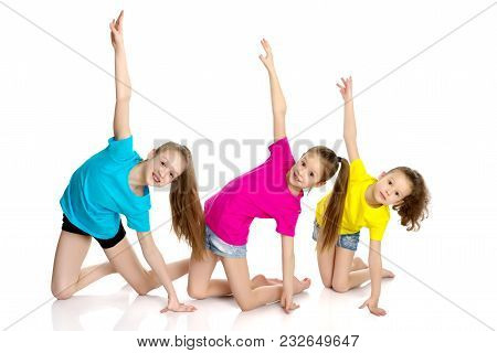 A Group Of Cheerful Little Girls-gymnasts Performing Various Gymnastic And Fitness Exercises. The Co
