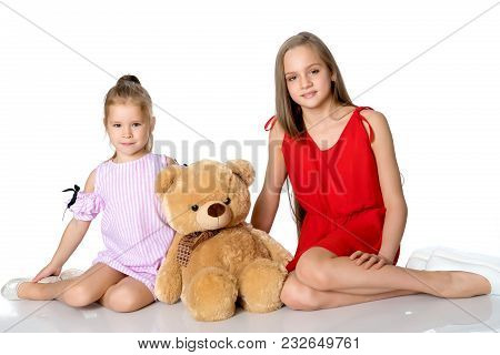 Lovely Little Girls. Next To A Large Teddy Bear On A White Background In The Studio. The Concept Of