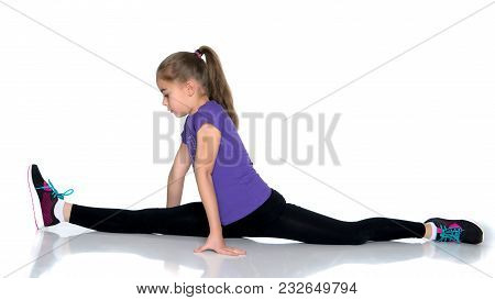 A Little Girl Performs A Gymnastic Twine. The Concept Of Fitness And Sports. Isolated On White Backg