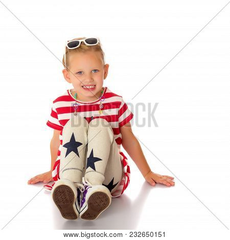 Beautiful Little Girl Is Sitting On The Floor In The Studio. The Concept Of A Happy Childhood, Beaut