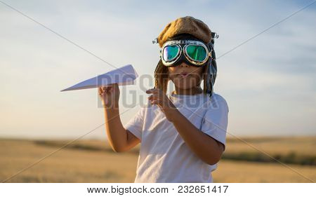 Imagination, Little boy wearing helmet and dreams of becoming an aviator while playing a paper plane at sunset