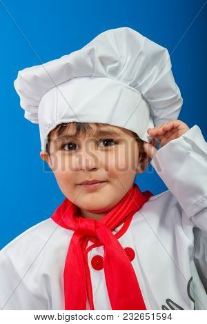 Cuisine, The little boy in a suit of the cook. adorable little boy in chef hat and apron smiling at camera in kitchen. boy in chef's hat