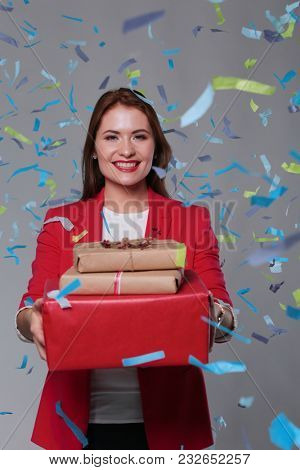 Beautiful happy woman with gift box at celebration party with confetti . Birthday or New Year eve celebrating concept