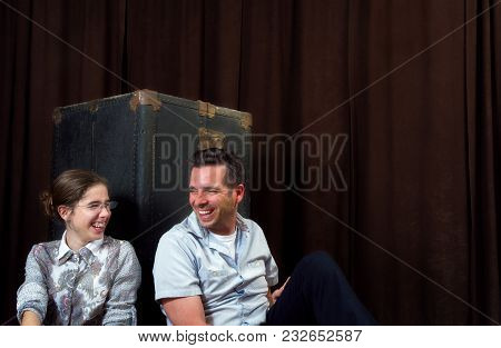 A Man And Girl Both Lean Against A Steamer Trunk Standing On End.  They Are Looking At Each Other An
