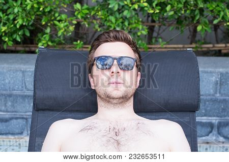 Content Caucasian Man In A Swimming Pool. He Is Enjoying His Time During Vacation In Summer.