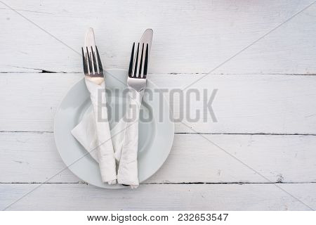 White Plate And Knife With Forks On Wooden Table. No Food. Wait For Your Dinner