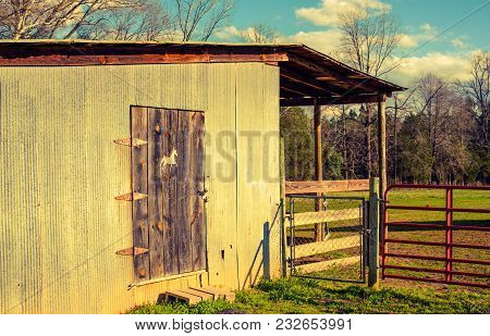 A Closeup Of An Old Wooden Barn And Gate With A Wooden Door With A Horse Emblem In Golden Retro Colo