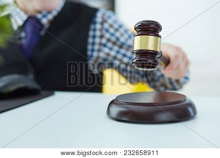 Little Boy Plays In The Lawyer Or Judge. Hand's Striking The Gavel On Sounding Block, Working At Cou