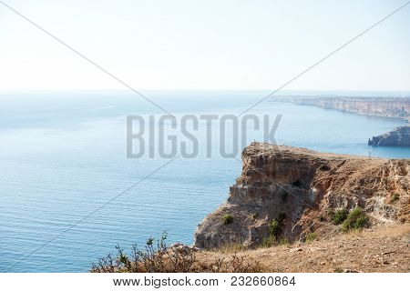 Perspective View Of Blue Water Washing Rocks Of White Cliffs On Shoreline.
