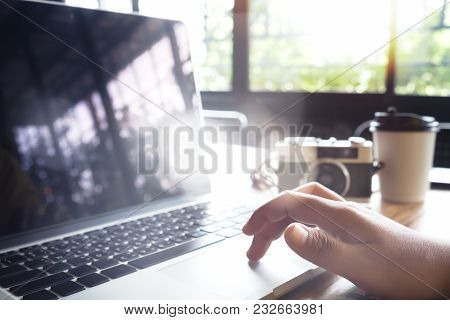 Hipster Woman Traveler Using Laptop Computer In Cafe. Young Woman Photographer Working At Coffee Sho