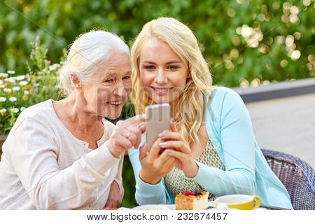 family, generation and people concept - happy smiling young daughter and senior mother with smartphone at cafe or restaurant terrace