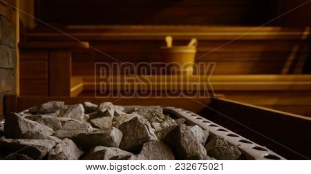 Wooden Bathhouse With A Heating Pot Filled With Stones, Close Up. Wooden Sauna Interior With Equipme