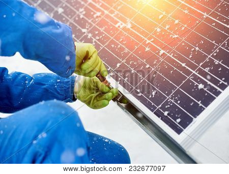 Close-up of hands worker installing solar panels in snowy weather. Worker with tools maintaining photovoltaic panel. A bit of snow on solar panels poster