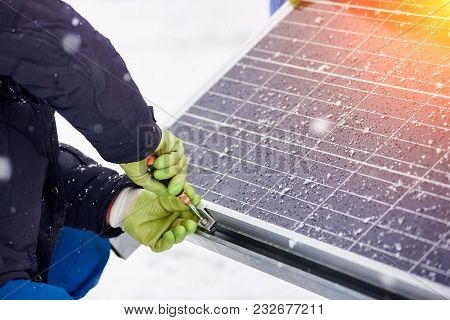 Hands Of Worker Installing Solar Panels In Snowy Weather. Worker With Tools Maintaining Photovoltaic