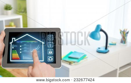 smart home and technology concept - close up of male hands pointing finger to tablet pc computer with house settings on screen over kids room background