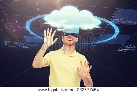 3d technology, virtual reality, computing, entertainment and people concept - happy young man in virtual reality headset or 3d glasses playing game over black background with screens and cloud