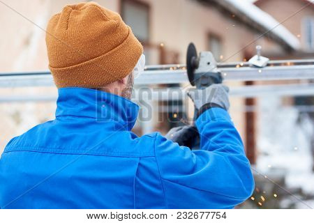 Male Technician In Blue Suit Cutting Metal With Cutting Wheel Getting Ready To Install Photovoltaic