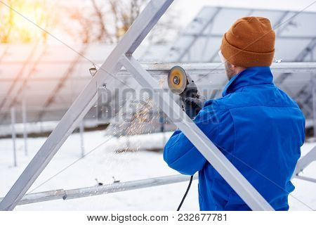 Rearview Shot Of A Professional Electricity Technician Installing Solar Panels Outdoors In Winter Co