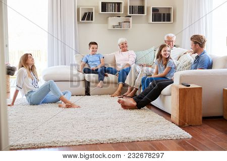 Multi Generation Family Relaxing On Sofa At Home Together