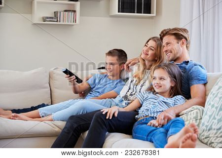 Family Sitting On Sofa At Home Watching TV Together