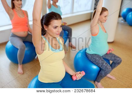 pregnancy, sport, fitness, people and healthy lifestyle concept - group of happy pregnant women with dumbbells on exercise ball in gym